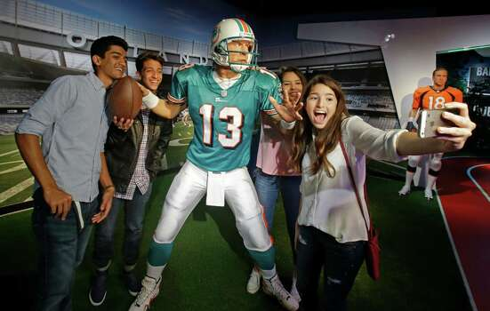 Visitors take a selfie with a wax figure of former NFL quarterback Dan Marino at Madam Tussauds wax museum in Orlando, Florida. The wax museum includes a figure of Juan Ponce de Leon, who led the first European expedition to Florida. A dark, submarine-inspired thrill ride in California and swank new offerings at Downtown Disney all top the summers must-do list for theme park and amusement fans. Photo: John Raoux /Associated Press / AP
