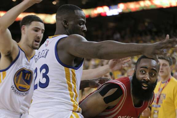 Rockets James Harden is guarded by Warriors Klay Thompson (11) and Draymond Green (23) in the fourth period during Game 1 of the Western Conference Finals on Tuesday, May 19, 2015 in Oakland, Calif.