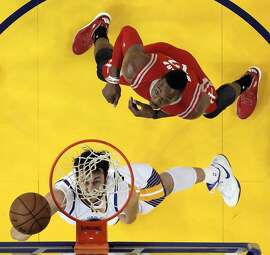 Andrew Bogut (12) shoots while defended by Dwight Howard (12) during the first half as the Golden State Warriors played the Houston Rockets in Game 1 of the Western Conference finals at Oracle Arena in Oakland, Calif., on Tuesday, May 19, 2015. The Warriors defeated the Rockets 110-106.