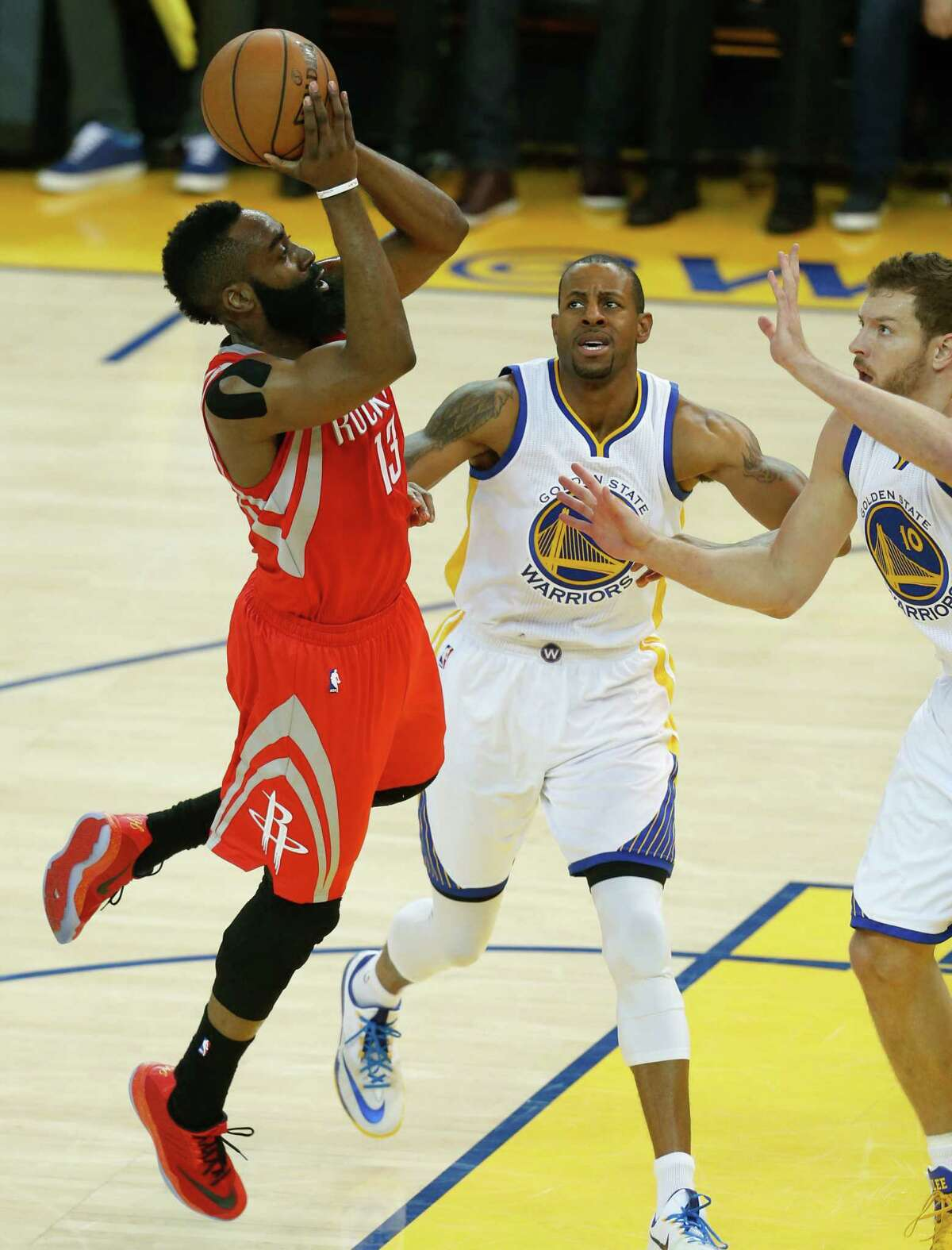 Rockets guard James Harden, left, shoots over the Warriors' Draymond Green, center, and David Lee to score two of his 28 points in Tuesday night's game.