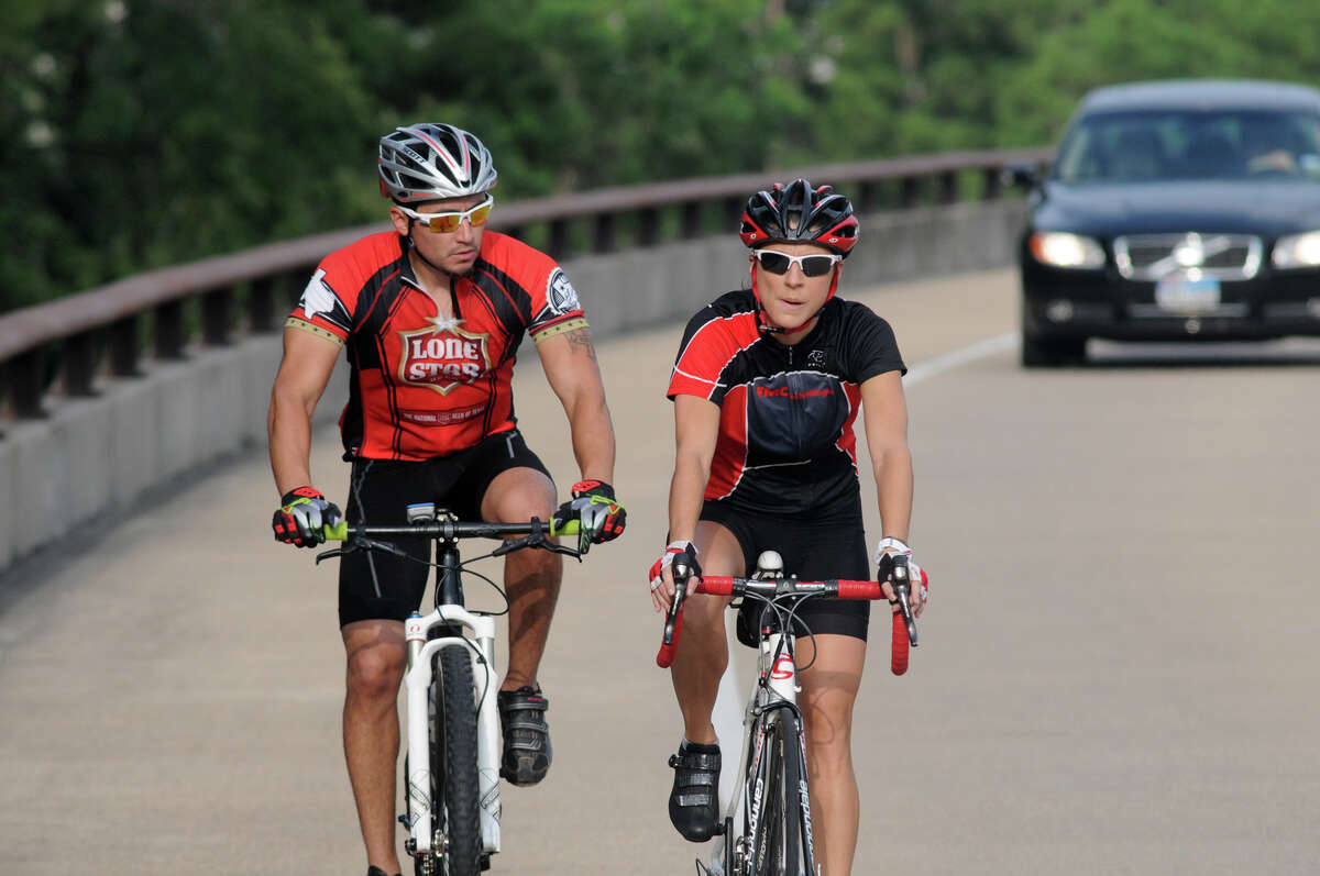 Candice Adams, from right, a member of the board of directors of The Woodlands Cycling Club, bikes along Lake Woodlands Parkway on her Friday ride with Tim Palacios.