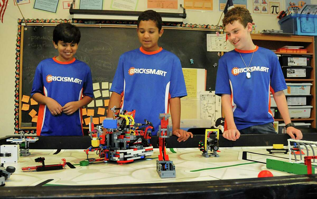 Vali Khan, Kabir Jolly, and Nick Franken watch the computer controlled Lego robotic at the Rubicon Academy, 14211 Horseshoe Bend in south Montgomery County, robotics team practice. Photograph by David Hopper.