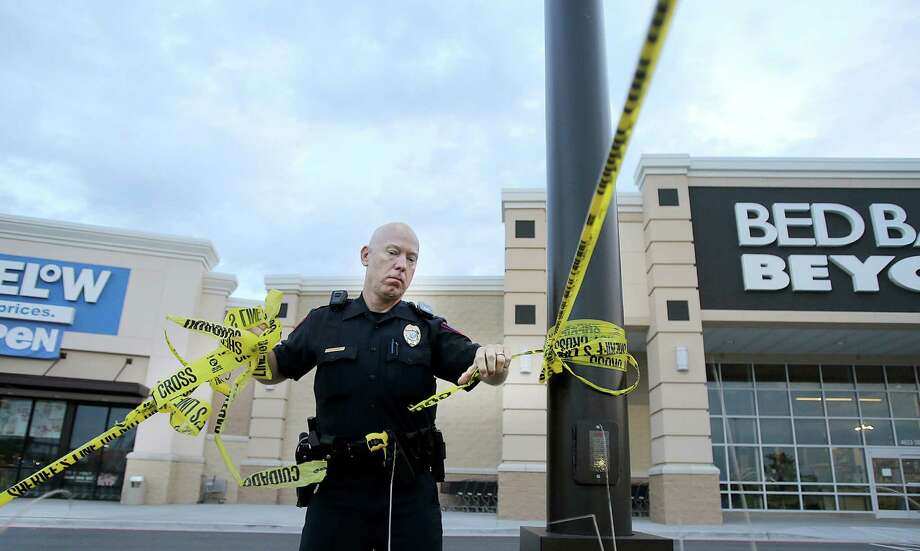 A Waco police officer takes down crime scene tape, Wednesday, May 20, 2015, as they re-open Central Texas Market Place after Sunday's shooting in Waco, Texas.  A deadly weekend shootout involving rival motorcycle gangs apparently began with a parking dispute and someone running over a gang member's foot, police said Tuesday.  (Jerry Larson/Waco Tribune Herald, via AP) Photo: Jerry Larson, Associated Press / Waco Tribune-Herald