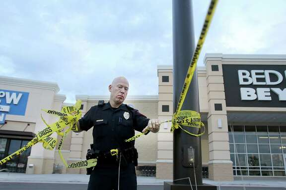 A Waco police officer takes down crime scene tape, Wednesday, May 20, 2015, as they re-open Central Texas Market Place after Sunday's shooting in Waco, Texas.  A deadly weekend shootout involving rival motorcycle gangs apparently began with a parking dispute and someone running over a gang member's foot, police said Tuesday.  (Jerry Larson/Waco Tribune Herald, via AP)
