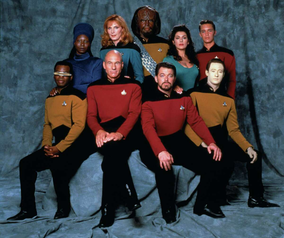 Promotional portrait of the cast of 'Star Trek: The Next Generation,' California, 1987. Pictured are from left, front row, American actor LeVar Burton (as Lieutenant Commander Geordi La Forge), British actor Patrick Stewart (as Captain Jean-Luc Picard), and American actors Jonathan Frakes (as Commander William T. Riker) and Brent Spiner (as Lieutenant Commander Data); from left, back row, American actors Whoopi Goldberg (as Guinan), Gates McFadden (as Doctor Beverly Crusher), and Michael Dorn (as Lieutenant Worf), British-American actress Marina Sirtis (as Counselor Deanna Troi), and American actor Wil Wheaton (as Wesley Crusher).