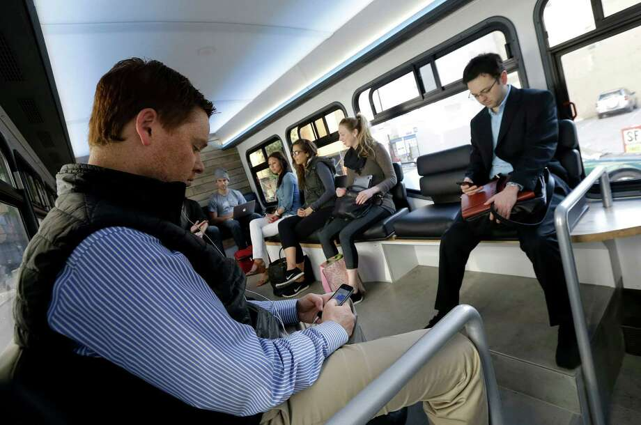 In this April 14, 2015 photo, Leap commuters use their smartphones during a bus ride in San Francisco. A company called Leap, a bus company that offers rides with spacious seating, free Wi-Fi and attendants who deliver snacks, launched the service last month with morning and evening commutes that follow public bus routes between the tony Marina district and the heart of downtown San Francisco. (AP Photo/Jeff Chiu) Photo: Jeff Chiu / Associated Press / AP