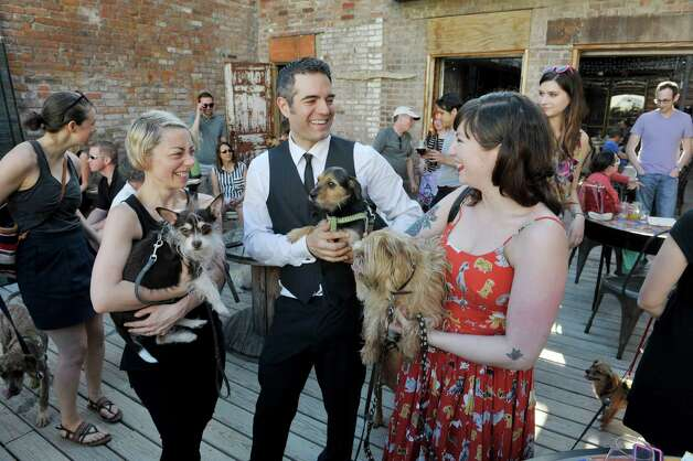 Lucas Confectionery owners, Heather LaVine, left, holding Charlie, and Vic Christopher, holding Groucho, talk with Paula Matt, owner of pet boutique henry Loves Betty, holding Henry, visit with each other at Yappy Hour at  Lucas Confectionery on Sunday, May 17, 2015, in Troy, N.Y.  Matt is the event sponsor of the Yappy Hour.  The wine bar has a weekly happy hour for dogs and their owners.    (Paul Buckowski / Times Union) Photo: PAUL BUCKOWSKI / 00031867A