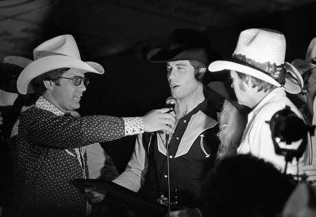 "John Travolta, center, and Mickey Gilley (right) at the Houston movie premiere party for ""Urban Cowboy"" at Gilley's club. Photo: Larry Reese, File  / Houston Chronicle"