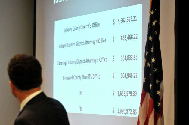 U.S. Attorney Richard Hartunian shows a slide that lists the amount of money going to different agencies during a press conference to announce the distribution of forfeited assets on Wednesday, May 20, 2015, in Albany, N.Y.  The funds were seized in an internet gambling and money laundering case.  (Paul Buckowski / Times Union) Photo: PAUL BUCKOWSKI, Albany Times Union / 00031927A
