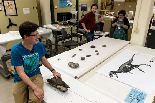Brandon Peecook, left, a University of Washington graduate student, and Dr. Christian Sidor, right, Burke Museum curator of vertebrate paleontology, show off the first dinosaur fossil ever found in Washington state: an 80-million-year-old partial left femur bone of a theropod dinosaur, photographed Wednesday, May 20, 2015, at the Burke Museum in Seattle, Washington. The bone was collected by Burke Museum paleontologists on the shore of Sucia Island State Park in the San Juan Islands in May 2012. The rest of the two-legged, carnivorous dinosaur was likely washed away or carried away by scavengers. The fossil will be on display in the Burke Museum's lobby beginning Thursday, May 21. (Jordan Stead, seattlepi.com) Photo: JORDAN STEAD, SEATTLEPI.COM