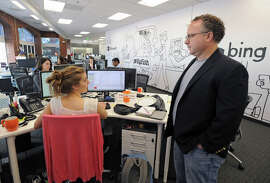 Kevin Buerger (right) executive vice president of British marketing firm Jellyfish, talks with strategist Kelly Pollhammer at the Baltimore office.