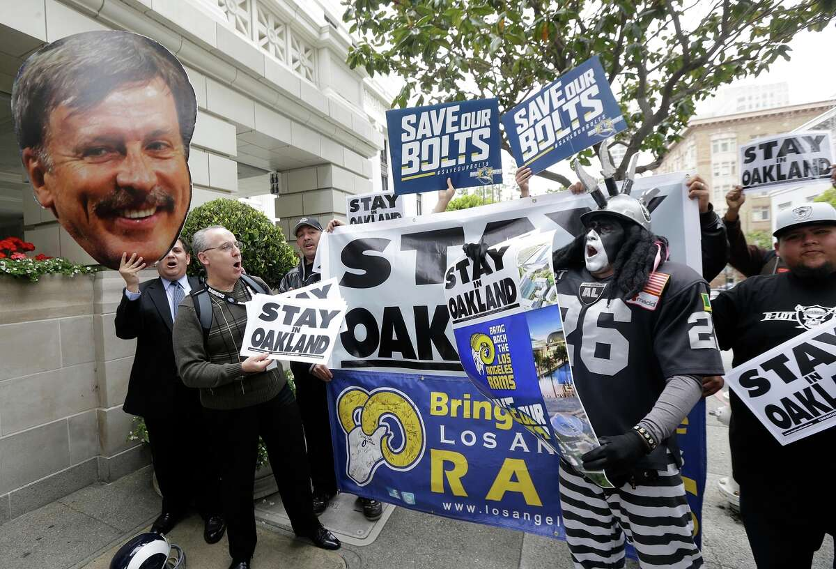 A photo of St. Louis Rams owner Stan Kroenke is held up by Rams fans as they rally with San Diego Chargers and Oakland Raiders fans Tuesday outside the NFL's Spring Meetings in S.F.
