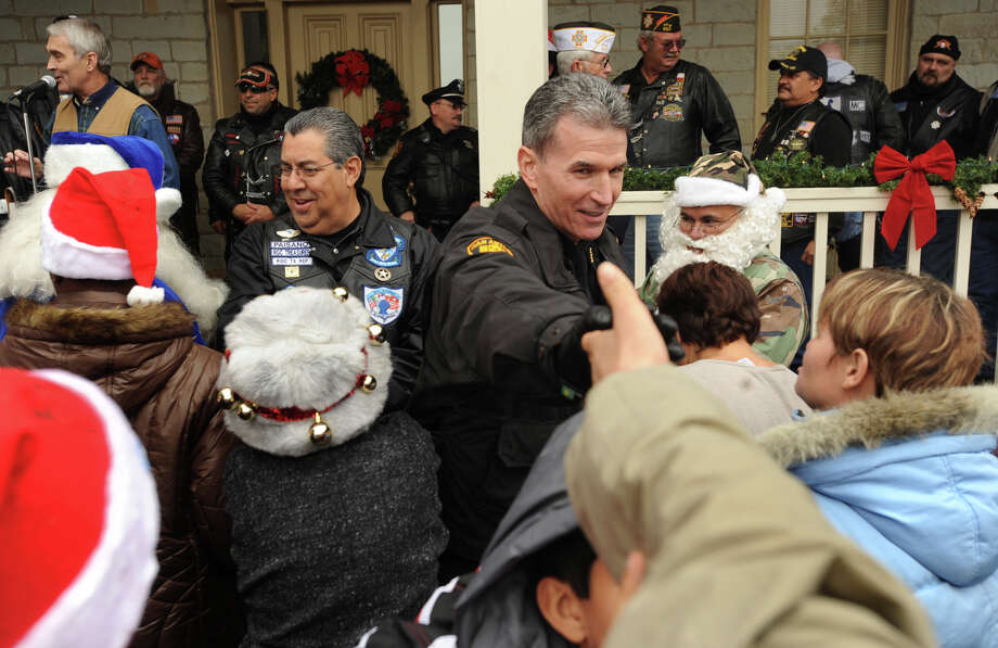 San Antonio Police Chief William McManus shakes hands with children of the Mission Road Developmental Center after the annual Blue Knights Christmas Toy Run on Saturday, Dec. 12, 2009. About 125 motorcyclists, classic cars and a fire engine participated in the event, which culminated in the delivery of gifts for children at the MRDC facility. BILLY CALZADA / gcalzada@express-news.net Photo: BILLY CALZADA, STAFF / SAN ANTONIO EXPRESS-NEWS / gcalzada@express-news.net