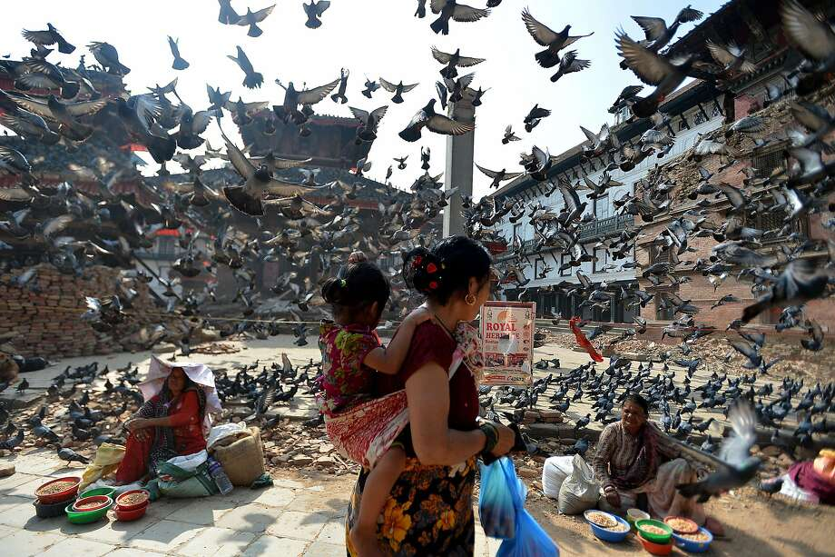 Flying pigeons pass over Nepalese street vendors near the earthquake damaged UNESCO World Heritage Site, Durbar Square in Kathmandu on May 20, 2015. Nearly 8,500 people have now been confirmed dead in the disaster, which destroyed more than half a million homes and left huge numbers of people without shelter with just weeks to go until the monsoon rains. Photo: Ishara S.kodikara, AFP / Getty Images
