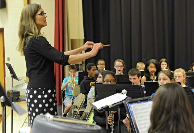 """Music teacher Terri Korb goes over a few things after composer Kevin Mixon of Syracuse worked with 7th grade band members who are rehearsing one of his pieces, """"Junkyard Jam,"""" for a concert on May 28 at Sand Creek Middle School on Wednesday, May 20, 2015 in Colonie, N.Y. (Lori Van Buren / Times Union) Photo: Lori Van Buren / 00031920A"""