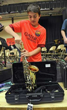 """John Brunner, 13,  puts away his alto saxophone after composer Kevin Mixon of Syracuse worked with the 7th grade band members who are rehearsing one of his pieces, """"Junkyard Jam,"""" for a concert on May 28 at Sand Creek Middle School on Wednesday, May 20, 2015 in Colonie, N.Y. (Lori Van Buren / Times Union) Photo: Lori Van Buren / 00031920A"""