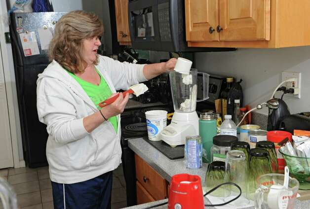 Jill Sharp makes a smoothie in her home on Wednesday, May 13, 2015 in Westerlo, N.Y. Jill and her sister Tami McDonald fear they have inherited heart disease. (Lori Van Buren / Times Union) Photo: Lori Van Buren / 00031771A