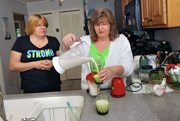 Tami McDonald of Albany, left, and her sister Jill Sharp make smoothies in Jill's kitchen on Wednesday, May 13, 2015 in Westerlo, N.Y. Jill and Tami fear they have inherited heart disease. (Lori Van Buren / Times Union) Photo: Lori Van Buren / 00031771A