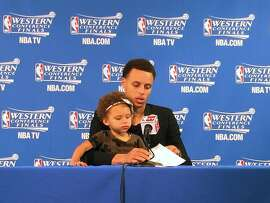 This image provided by SFBay.ca, shows Golden State Warriors' Stephen Curry with his daughter Riley during the post game press conference after the first game of their Western Conference finals of the NBA Playoffs in Oakland, California, on Tuesday, May 19, 2015. The Warriors defeated the Houston Rockets 110-106. (Sarah Todd / SFBay.ca via AP)