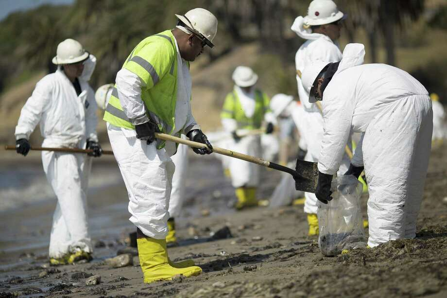GOLETA, CALIFORNIA - MAY 20:  A crew cleans oil from the beach at Refugio State Beach on May 20, 2015 north of Goleta, California. About 21,000 gallons spilled from an abandoned pipeline on the land near Refugio State Beach, spreading over about four miles of beach within hours. The largest oil spill ever in U.S. waters at the time occurred in the same section of the coast where numerous offshore oil platforms can be seen, giving birth to the modern American environmental movement.  (Photo by David McNew/Getty Images) Photo: David McNew, Stringer / Getty Images / 2015 David McNew