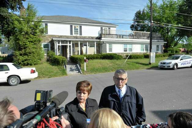 Colonie Town Supervisor Paula Mahan, left, and town attorney Michael Maggiulli talks to members of the press  at the scene of a building code enforcement at a home located at 1278 Central Ave., in background, on Wednesday, May 20, 2015, in Colonie, N.Y.  Colonie Town attorney, Michael Maggiulli, said that the first floor has been carved up into 15 bedrooms with 37 to 40 beds.  (Paul Buckowski / Times Union) Photo: PAUL BUCKOWSKI / 00031924A