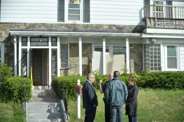 Colonie  town attorney Michael Maggiulli, left, and Colonie Town Supervisor Paula Mahan, far right, talk with a town police officer and a town building inspector at the scene of a building code enforcement at a home located at 1278 Central Ave., in the background, on Wednesday, May 20, 2015, in Colonie, N.Y.  Colonie Town attorney, Michael Maggiulli, said that the first floor has been carved up into 15 bedrooms with 37 to 40 beds.  (Paul Buckowski / Times Union) Photo: PAUL BUCKOWSKI / 00031924A