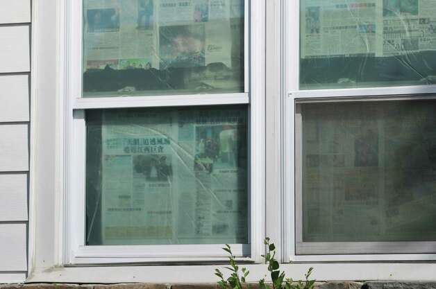 A view of the home located at 1278 Central Ave., on Wednesday, May 20, 2015, in Colonie, N.Y.  The Town of Colonie building inspectors shut down the first floor of the home because of code violations.  Newspapers were used by occupants as shades for the windows.  Colonie Town attorney, Michael Maggiulli, said that the first floor has been carved up into 15 bedrooms with 37 to 40 beds.  (Paul Buckowski / Times Union) Photo: PAUL BUCKOWSKI / 00031924A
