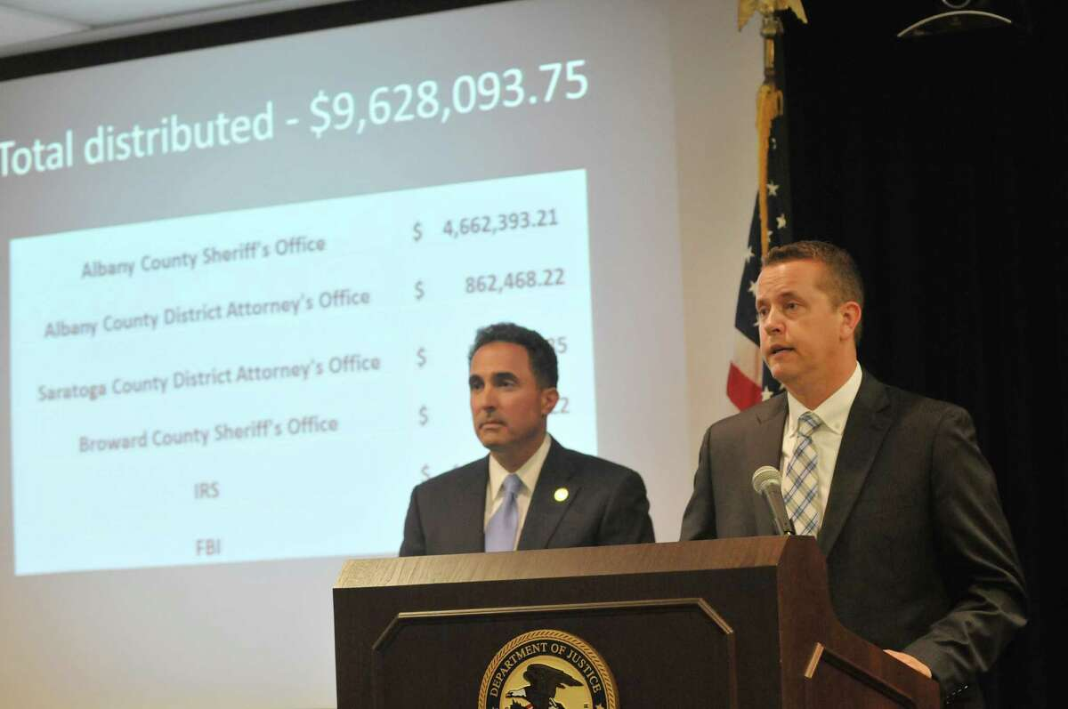 Craig Apple, Sr., foreground, Albany County Sheriff, and U.S. Attorney Richard Hartunian, background, take part in a press conference to announce the distribution of forfeited assets to local agencies on Wednesday, May 20, 2015, in Albany, N.Y. The funds were seized in an internet gambling and money laundering case. (Paul Buckowski / Times Union)