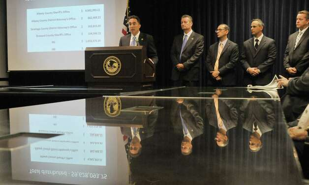 U.S. Attorney Richard Hartunian, left,  addresses those gathered at a press conference to announce the distribution of forfeited assets to local agencies on Wednesday, May 20, 2015, in Albany, N.Y.  The funds were seized in an internet gambling and money laundering case.  Also pictured are from left to right, United States Marshal David McNulty, Andrew Vale, special agent in charge of the Albany Division of the FBI, Thomas Fattorusso, IRS supervisory special agent, and Craig Apple, Sr., Albany County Sheriff.  (Paul Buckowski / Times Union) Photo: PAUL BUCKOWSKI / 00031927A