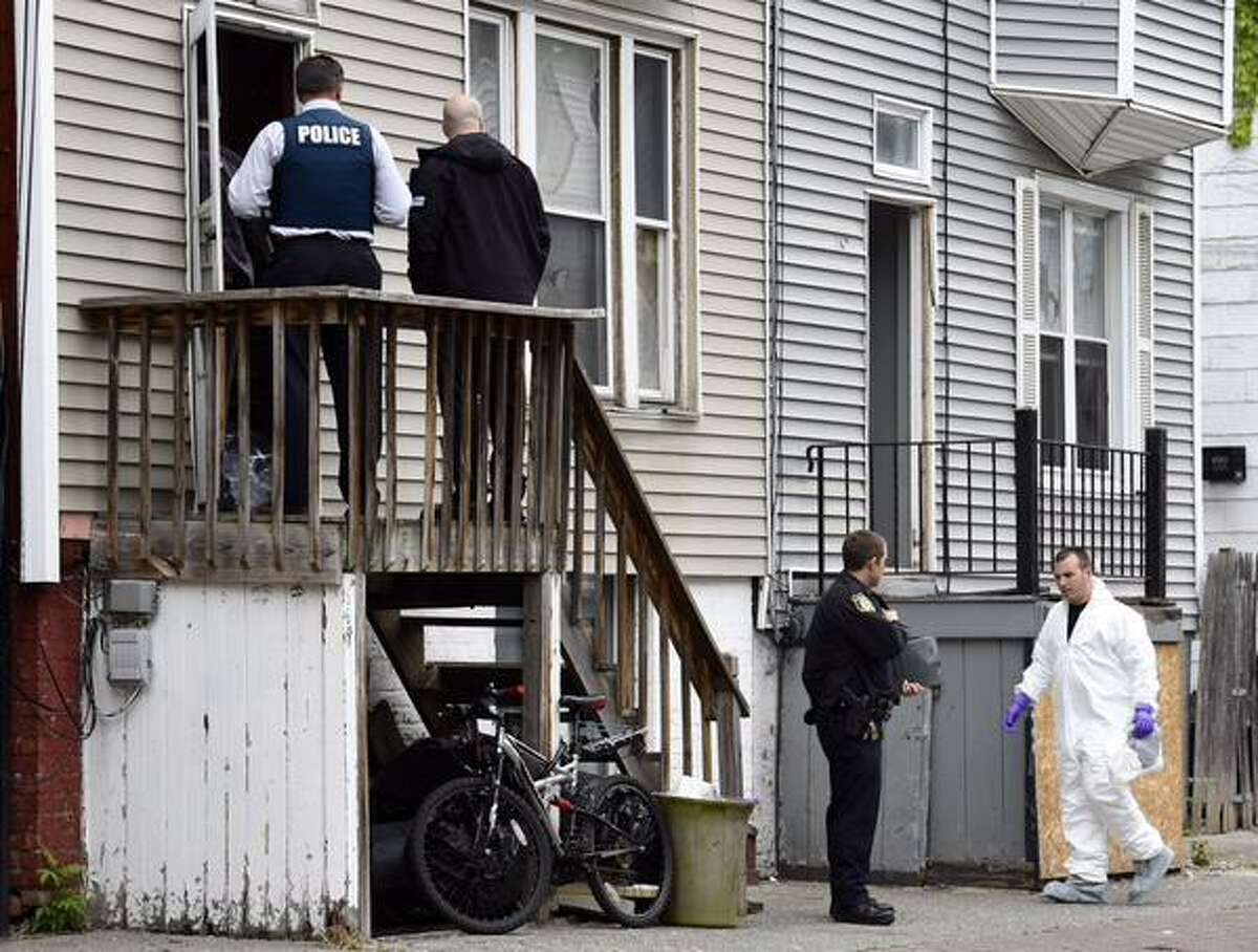 Detectives and evidence technicians examine the scene of a killing at 369 First St., Ablany. A man was killed inside the building late Wednesday night. (Skip Dickstein / Times Union)