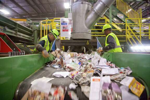 Waste Management employees work quickly to remove non-recyclable materials from a conveyor belt filled with recyclable garbage.