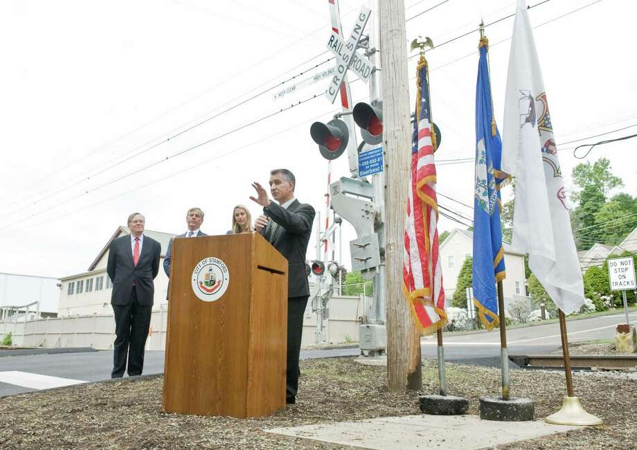 Stamford Mayor David Martin, Commissioner of Connecticut DOT James P. Redeker and State Representative Caroline Simmons listen to State Senator Carlo Leone speak about the new railroad crossing on Riverbend Drive South in Stamford. Thursday, May 21, 2015 Photo: Scott Mullin / The News-Times Freelance