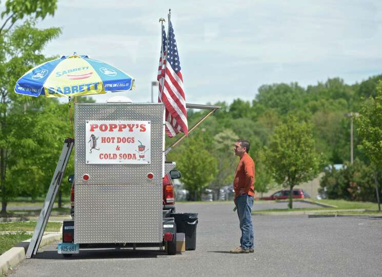 Mike Russell, of Torrington, looks over the menu of Poppy's hot dog stand during his lunch break, on