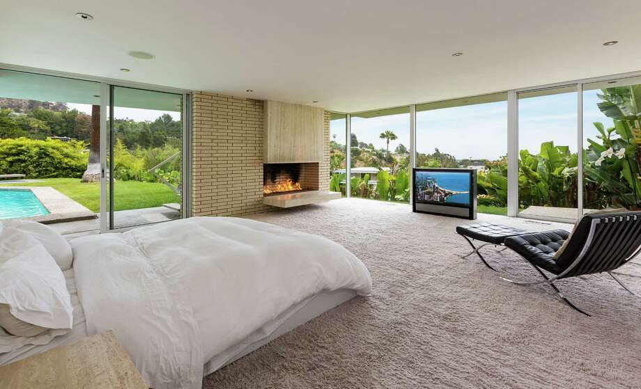 This four-bedroom, five-bath, 4,300-square-foot Beverly Hills home was designed and built for Houston's own eccentric mogul Howard Hughes in 1960. The home comes with a state-of-the-art security system, an indoor gym, steam showers, and indoor and outdoor fireplaces and of course, a pool. It's a steal for $11.5 million to live in the 90210 zip code. Photo: Rodeo Realty / Berlyn Photography 2015