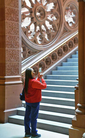 AARP care givers advocate Loraine Assent of Brooklyn takes a moment to photograph on a staircase during public advocacy day at the Capitol Tuesday May 19, 2015, in Albany, NY.   (John Carl D'Annibale / Times Union) Photo: John Carl D'Annibale, Albany Times Union