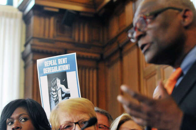 A supporter of rent regulation holds up a sign behind Assembly Democrats as they hold a press conference on rent regulations at the Capitol on Tuesday, May 19, 2015, in Albany, N.Y.  (Paul Buckowski / Times Union) Photo: PAUL BUCKOWSKI, Albany Times Union / 00031902A
