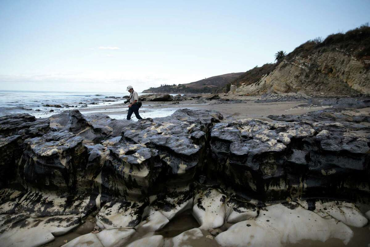 David Ledig, a national monument manager from the Bureau of Land Management, walks past rocks covered in oil at Refugio State Beach, north of Goleta, Calif., Thursday, May 21, 2015. More than 7,700 gallons of oil has been raked, skimmed and vacuumed from a spill that stretched across 9 miles of California coast, just a fraction of the sticky, stinking goo that escaped from a broken pipeline, officials said.