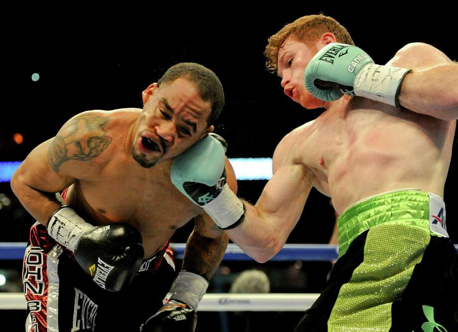 Canelo Alvarez, right, punches James Kirkland during the first round of their super welterweight match, Saturday, May 9, 2015, at Minute Maid Park in Houston. Alvarez won the fight with a knockout in the third round. Photo: Eric Christian Smith /For The Houston Chronicle / 2015 Eric Christian Smith