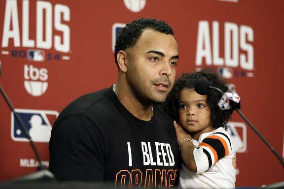Baltimore Orioles' Nelson Cruz holds his daughter, Giada, during a news conference following Game 3 of baseball's AL Division Series Sunday, Oct. 5, 2014, in Detroit. Baltimore defeated the Detroit Tigers, 2-1, to win the series 3-0. (AP Photo/Carlos Osorio)
