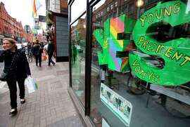 """A woman walks past a """"yes"""" banner for same-sex marriage outside the Green Party's office in Dublin."""