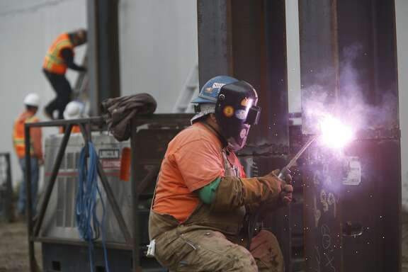 A Suffolk Construction laborer welds at the construction site at 360 Berry Street on Thursday, May 21, 2015 in San Francisco, Calif.