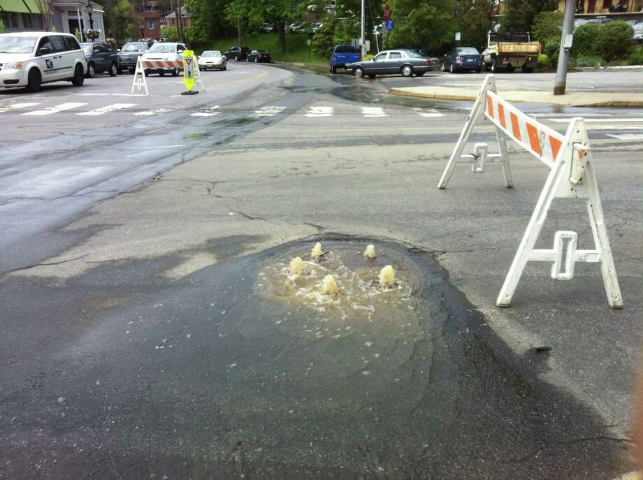 A water main break shattered the pavement at the intersection of Park Street and Elm on Thursday afternoon, snarling downtown traffic and leaving downtown businesses without water. Above, water from the break gushes up through a manhole cover at the corner of Pine and Park streets. Photo: Martin Cassidy / New Canaan News
