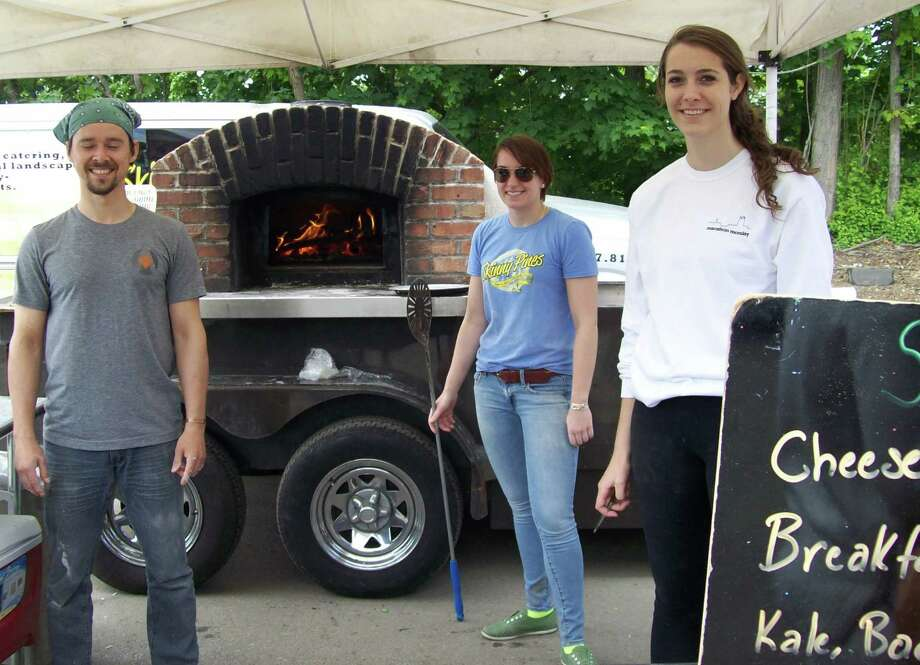 David Hornack, Maddie Prangley and Casey Boatwright were serving up Skinny Pines pizzas made in a mobile wood-fired brick oven on the opening day of the Westport Farmers' Market's new season. Photo: Anne M. Amato / westport news