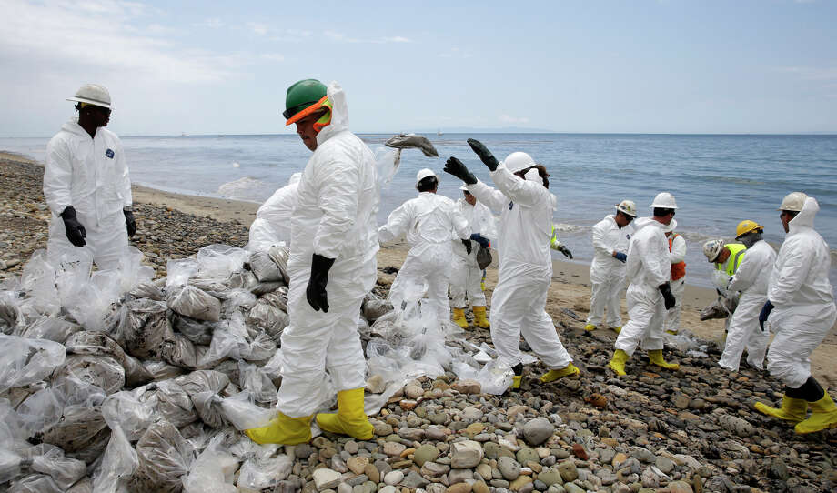 Clean up workers gather oil-contaminated sand bags at Refugio State Beach, north of Goleta, Calif., Thursday, May 21, 2015. More than 7,700 gallons of oil has been raked, skimmed and vacuumed from a spill that stretched across 9 miles of California coast, just a fraction of the oil escaped from a broken pipeline, officials said. Photo: Jae C. Hong / Associated Press / AP