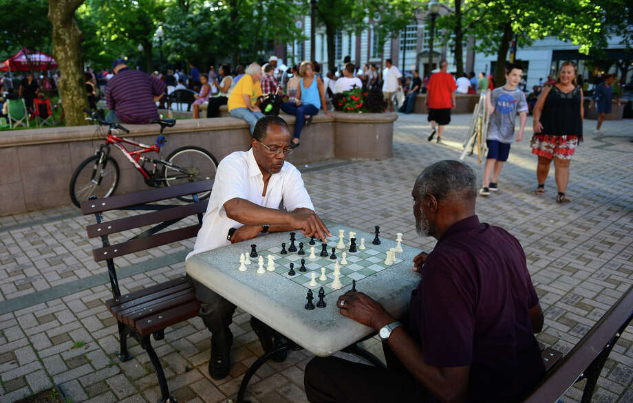 Robert Gayden makes a move as he plays chess against Sonny Walter on McLevy Green in downtown Bridgeport, Conn. Bridgeport has posted population gains according to the latest census report. Photo: Christian Abraham / Connecticut Post