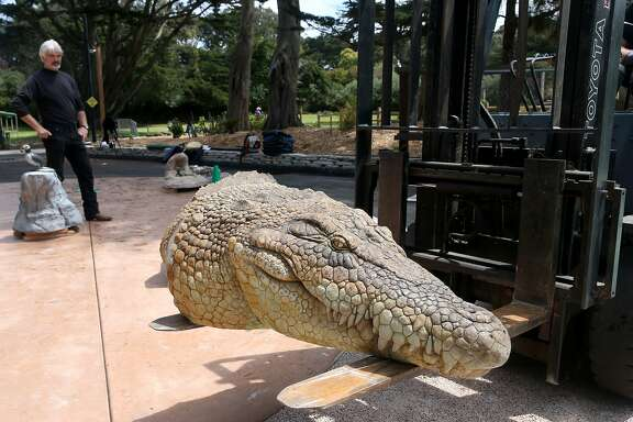 Sections of a large, lifelike salt water crocodile sculpture are unloaded and assembled at the San Francisco Zoo in San Francisco, Calif. on Thursday, May 21, 2015. Ron Holthuysen (left) and his Scientific Art Studio created the creatures for the zoo's Sculpture Learning Plaza which opens on June 6.
