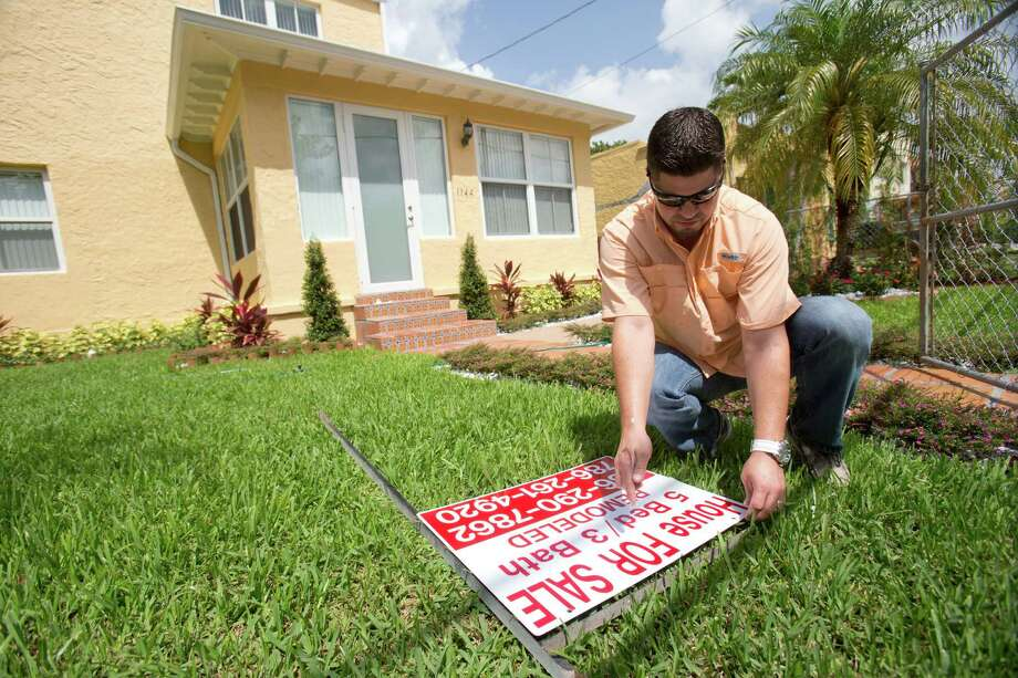 Robert Almirall, director of marketing and special assets coordinator for Mederos & Associates Real Estate Inc., prepares to put up a sign in front of a home in the Shenandoah neighborhood of Miami. Sellers who want their homes to stand out need to take certain steps to be sure the process goes smoothly and that they get an offer that meets their needs. Photo: Wilfredo Lee /Associated Press / AP