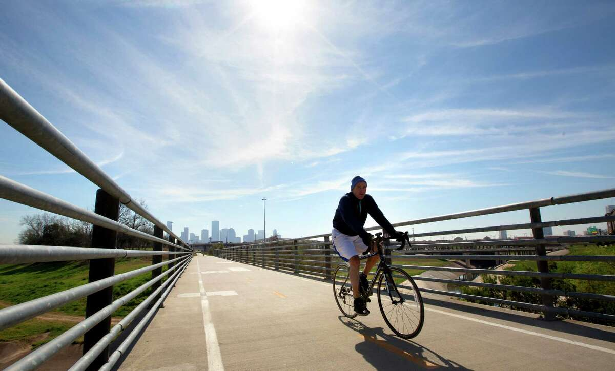 Blue skies provide a backdrop for a cyclist as he rides his bike along a paved path in the Heights.