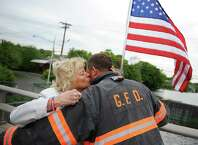 Late Selectman David Theis' longtime partner Kerrin Coyle kisses Cos Cob Volunteer Firefighter John Pugni after putting up the first of many American flags on the Mianus River Bridge on Route 1 in Greenwich, Conn. Thursday, May 21, 2015.  Cos Cob volunteer firefighters and friends of the late Selectman David Theis, including longtime partner Kerrin Coyle, hung flags on the bridge - a tradition started by Theis.
