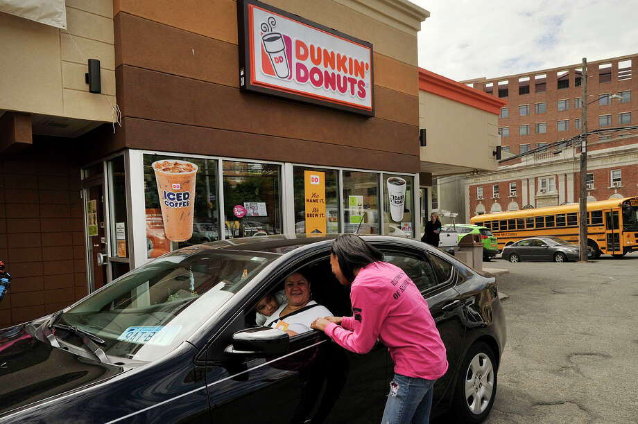 Laquariah Corder, a senior at Stamford Academy, participates in the Random Acts of Kindness Day by giving a $5 Dunkin' Donuts gift card to Rose Lopez outside the coffee shop on Prospect Street in downtown Stamford, Conn., on Thursday, May 21, 2015. Photo: Jason Rearick / Stamford Advocate